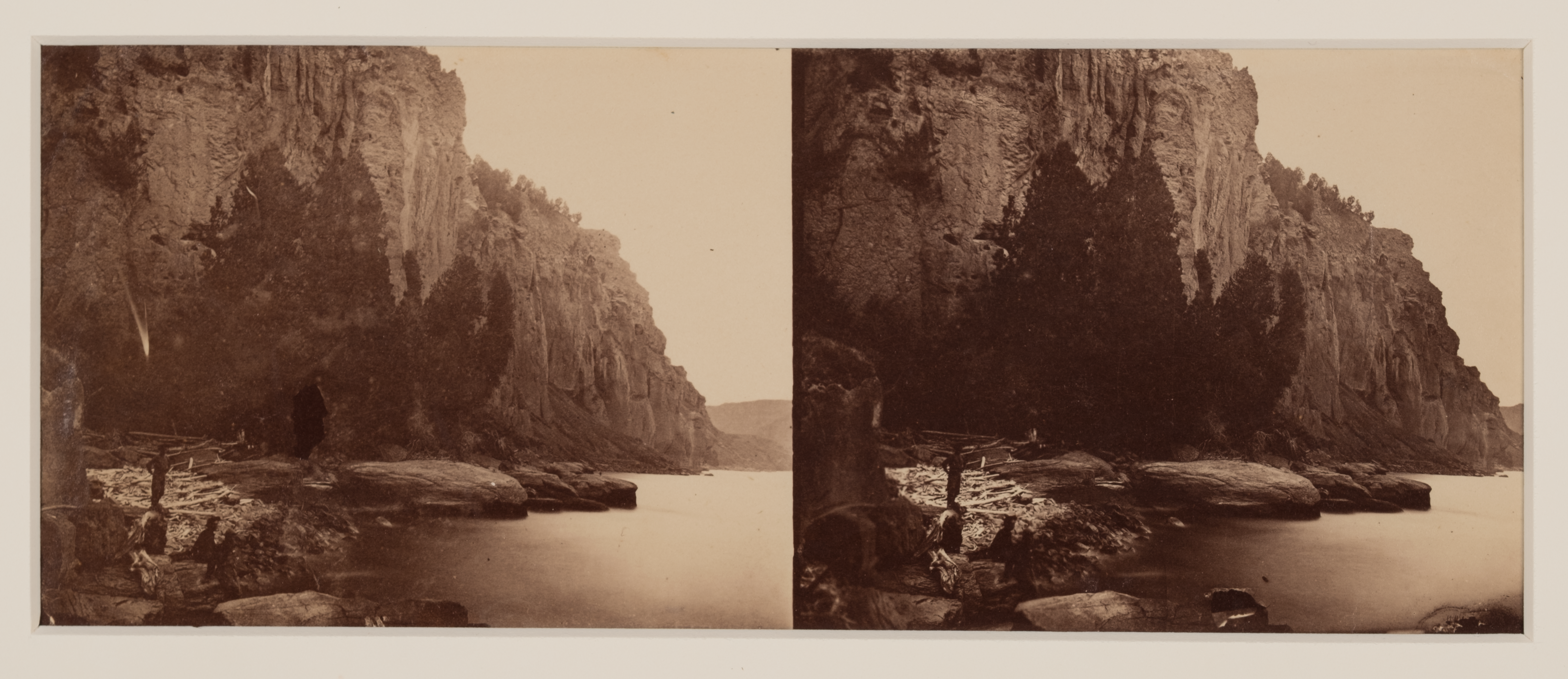 Side-by-side stereographs of a man near a river with cliffs and trees in the background